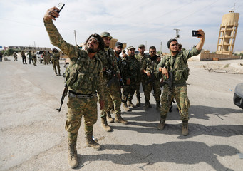 Turkey-backed Syrian rebel fighters take pictures with mobile phones at the border town of Tel Abyad