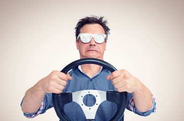 Emotional man in opaque aluminum glasses with steering wheel. Front view. Car driver concept