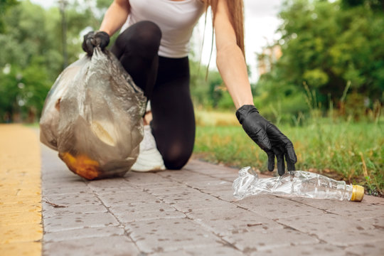 Plogging. Young girl volunteer in gloves running outdoors picking up litter plastic bottle close-up