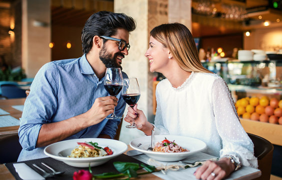 Paste and red wine. Young couple enjoying lunch in the restaurant. Lifestyle, love, relationships, food concept