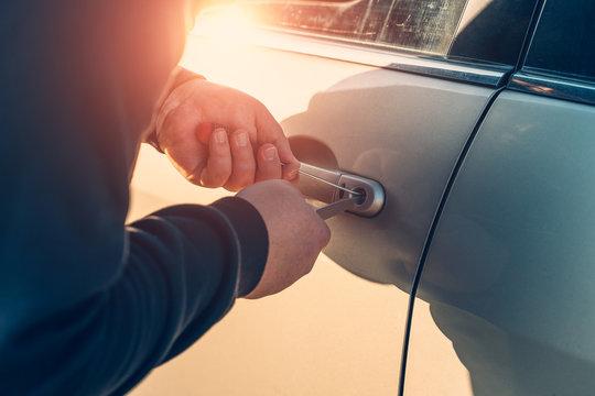 Car robber or thief trying to break auto door lock, close up. Car theft concept