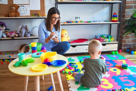 Young therapist woman speaking with child, counselor and behaviour correction at the office around toys
