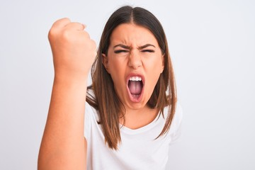 Portrait of beautiful and young brunette woman standing over isolated white background angry and mad raising fist frustrated and furious while shouting with anger. Rage and aggressive concept.