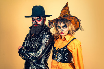 Cute man and woman wearing Halloween clothes. Portrait of happy young couple in Halloween with pumpkin.