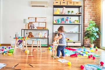 Beautiful toddler standing around lots of toys at kindergarten