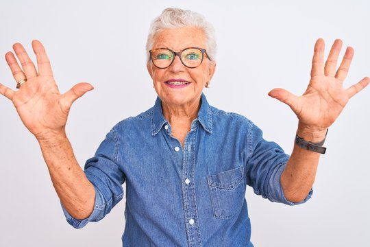 Senior grey-haired woman wearing denim shirt and glasses over isolated white background showing and pointing up with fingers number ten while smiling confident and happy.