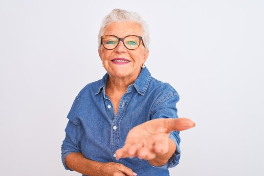 Senior grey-haired woman wearing denim shirt and glasses over isolated white background smiling cheerful offering palm hand giving assistance and acceptance.