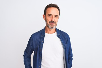 Middle age handsome man wearing blue denim shirt standing over isolated white background Relaxed with serious expression on face. Simple and natural looking at the camera.