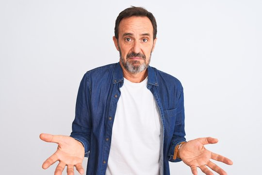 Middle age handsome man wearing blue denim shirt standing over isolated white background clueless and confused with open arms, no idea concept.