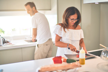 Middle age beautiful couple cooking together on the kitchen