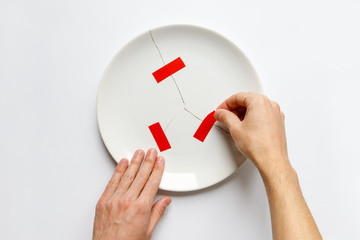 Top view of man hands holding a broken white plate, glues parts with red tape. Metaphor for divorce, relationships, friendships, crack in marriage. Isolated on white background, copy space.