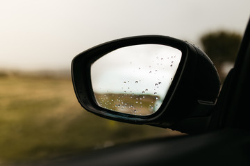 Rear view mirror seen through the glass. Wet car window. Close up rain drop. Car view see the mirror.