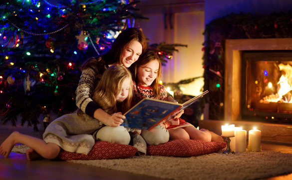 Happy young mother and her daughters reading a story book together by a fireplace in a cozy dark living room on Christmas eve. Celebrating Xmas at home.