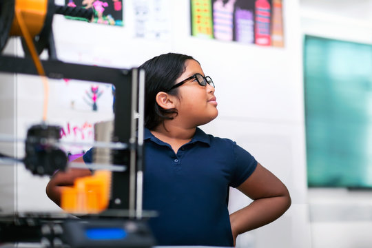 A confident latino student thinking about her 3D project in a after school program focusing on STEM.