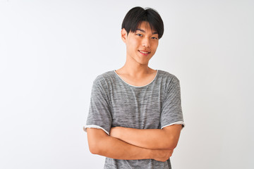 Young chinese man wearing casual t-shirt standing over isolated white background happy face smiling with crossed arms looking at the camera. Positive person.
