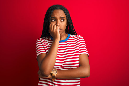 Young african american woman wearing striped t-shirt standing over isolated red background looking stressed and nervous with hands on mouth biting nails. Anxiety problem.