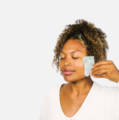 Mixed ethnicity woman using gua sha stone to massage her face / holistic wellness and self care concept