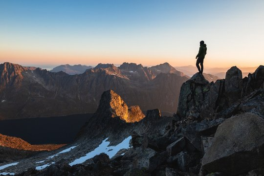 Horizontal shot of a male fearlessly standing on the top of a cliff enjoying the gorgeous view