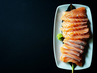Top view picture of Salmon sashimi on white plate isolated on black texture background.