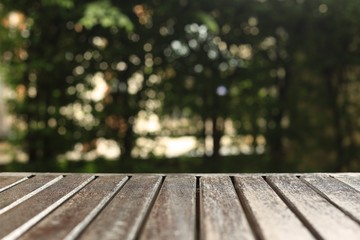 wooden floor background for products placement copy space. wood table in a garden. forest bokeh light background. warm tone image