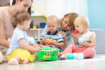 Adorable babies toddlers playing at home or kindergarten, cutting plastic vegetables and tasting these toys. Games in creche
