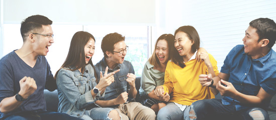 Banner of asian group of friends talking and laughing with happy in gathering meeting sitting at home feeling cheerful and enjoy game in leisure time together. People in blue or yellow wearing.