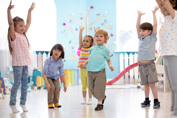 Group of preschool children doing gymnastics in kindergarten. Physical activity for kids in playschool