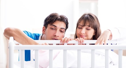 The happy young family at baby bed cot