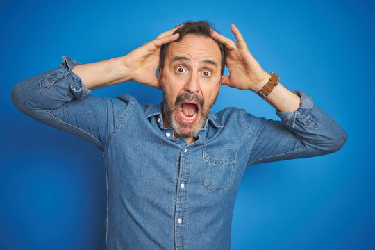 Handsome middle age senior man with grey hair over isolated blue background Crazy and scared with hands on head, afraid and surprised of shock with open mouth