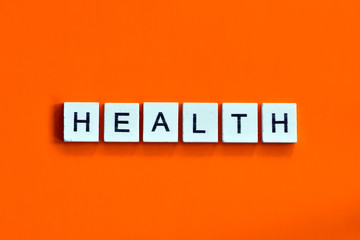 A homemade wooden tile with letters on a orange background, word health