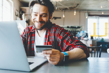 Portrait of man with stubble and flannel shirt. Smiling and shopping online with credit card