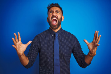 Young indian businessman wearing elegant shirt and tie standing over isolated blue background crazy and mad shouting and yelling with aggressive expression and arms raised. Frustration concept.
