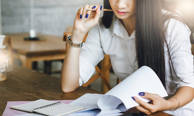 Young businesswoman thinking and read information from paper in hand