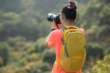 Woman photographer taking pictures in autumn forest