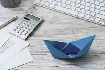 Modern office workspace with blue paper ship