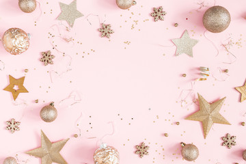 Christmas composition. Golden decorations on pastel pink background. Christmas, winter, new year concept. Flat lay, top view, copy space