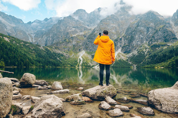 man in yellow raincoat taking picture on phone of lake in mountains