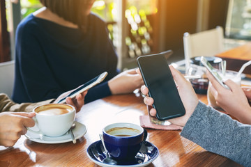 Closeup image of people using mobile phone and drinking coffee together in cafe