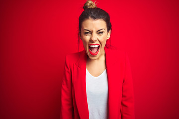 Young beautiful business woman standing over red isolated background angry and mad screaming frustrated and furious, shouting with anger. Rage and aggressive concept.