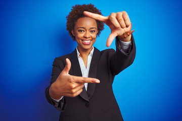 African american business executive woman over isolated blue background smiling making frame with hands and fingers with happy face. Creativity and photography concept.