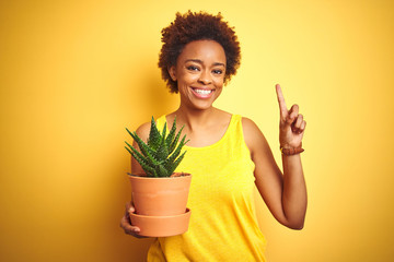 Young african american woman holding cactus pot over isolated yellow background surprised with an idea or question pointing finger with happy face, number one