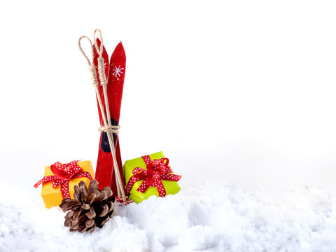 Gift boxes with ribbon, cone and pair of skis in snow isolated on white background.