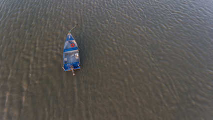 Aerial. An old fishing boat from above, on the Tejo River, in the Samouca Marina. Lisbon.