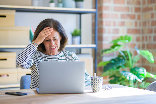 Middle age senior woman sitting at the table at home working using computer laptop stressed with hand on head, shocked with shame and surprise face, angry and frustrated. Fear and upset for mistake.