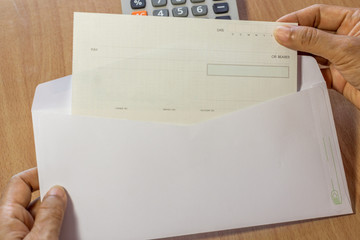 Female hands opening white envelope with cheque book in it, Laptop computer background. Achievement concept.