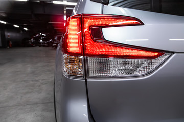 Close-up taillight of a new halogen silver crossover car. Exterior of a modern car.