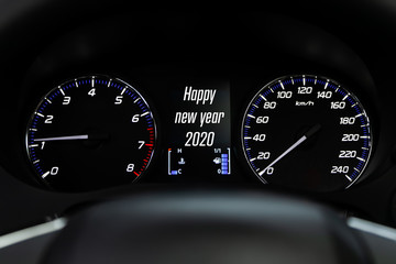 Close up Instrument automobile panel with Odometer, speedometer, tachometer, fuel level, which says Happy New Year 2020. The concept of the new year and Christmas in the automotive field.