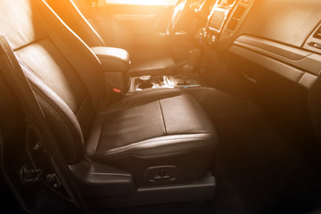 Close-up rear seat made of black leather with a head restraint, in the background passenger seats with seat belts. Luxury car interior
