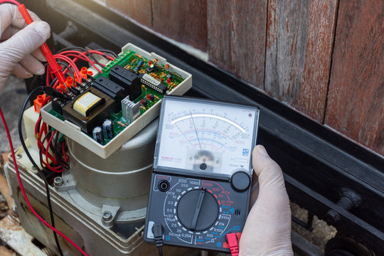 Closeup technician man hand repairing and checking  the functional of home electric auto door remote control by using multimeter. Maintenance and security system concept.