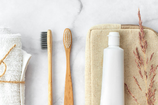 Set of eco-friendly toothbrushes, toothpaste and cotton towel on marble background. Dental and healthcare concept. Top view, flat lay.